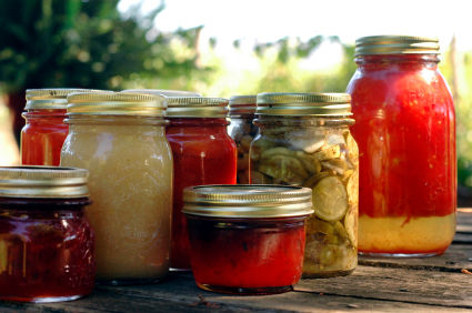 Homemade preserves sitting on a rustic table outside. Pickes, tomatoes, appplesauce, etc.